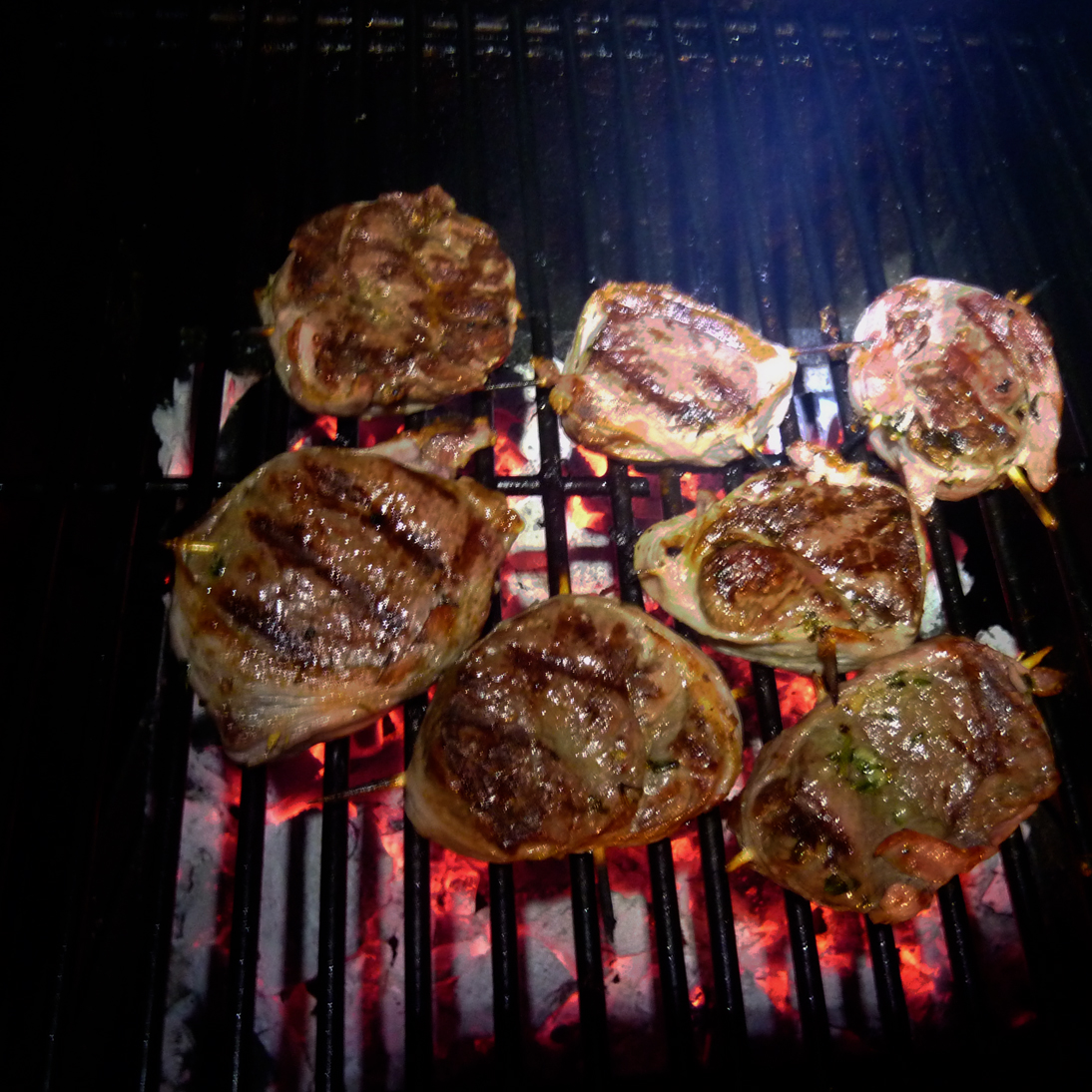 Bacon-wrapped rib-eye medallions on charcoal grill